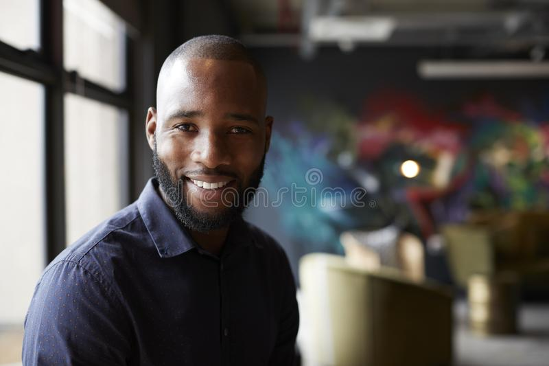 W połowie dorosły czarny męski kreatywnie w biurowym ogólnospołecznym terenie obraca kamera ono uśmiecha się, zakończenie w górę fotografia stock