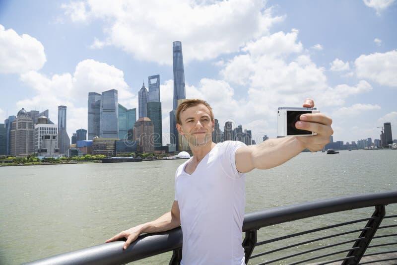 W połowie dorosły mężczyzna bierze selfie podczas gdy stojący ostro protestować przeciw Pudong linii horyzontu zdjęcie royalty free