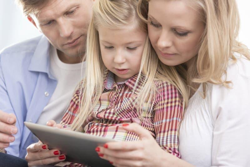 W połowie dorosły wychowywa używać pastylka peceta z córką w domu obraz stock