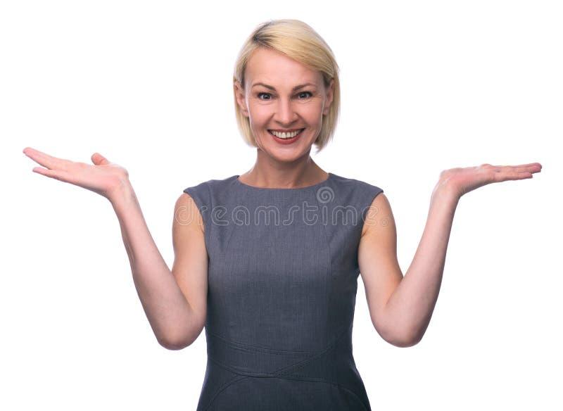 W połowie pełnoletnia kobieta gestykuluje z rękami i pokazuje równowagę zdjęcia stock