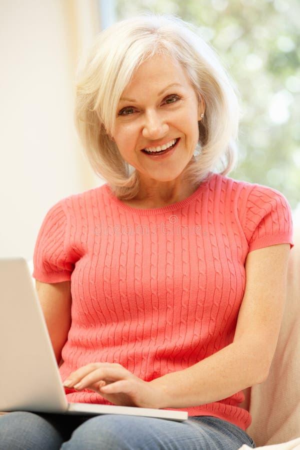 W połowie pełnoletnia kobieta używa laptop w domu zdjęcia royalty free