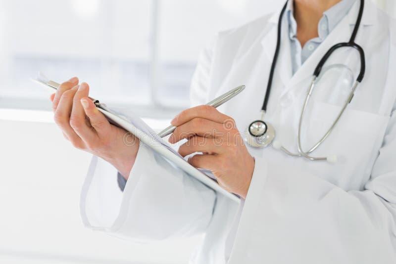 W połowie sekcja żeński doktorski writing donosi obraz stock