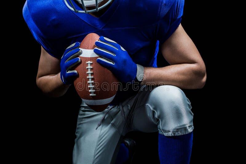 W połowie sekcja futbolu amerykańskiego gracza klęczenie podczas gdy trzymający piłkę zdjęcie stock