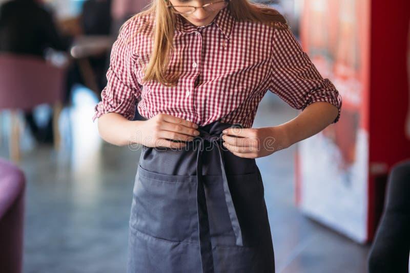 W połowie sekcja jest ubranym fartucha przy kawiarnią kelnerka obrazy stock