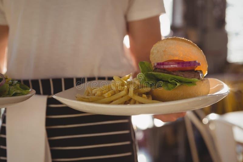 W połowie sekcja kelnera mienia talerz z hamburgerem i francuzów dłoniakami obrazy stock