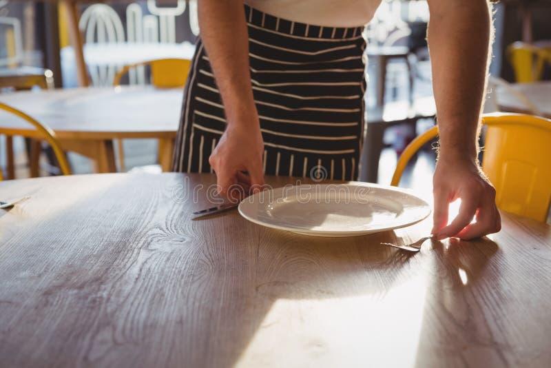 W połowie sekcja kelnera ułożenia talerz na stole zdjęcia royalty free