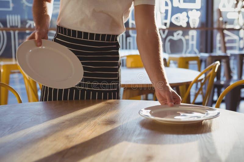 W połowie sekcja kelnera ułożenia talerze na stole zdjęcia stock