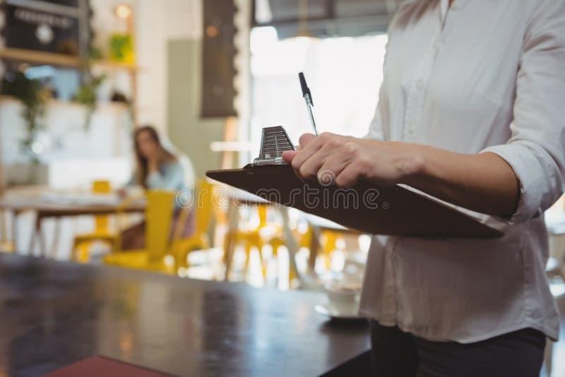 W połowie sekcja kelnerka z schowkiem w kawiarni zdjęcie royalty free