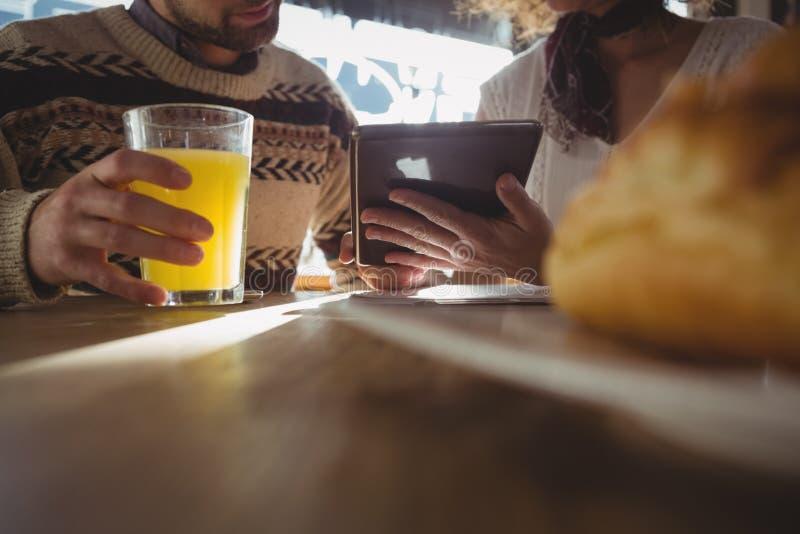 W połowie sekcja kobieta z mężczyzna używa pastylkę w kawiarni fotografia royalty free