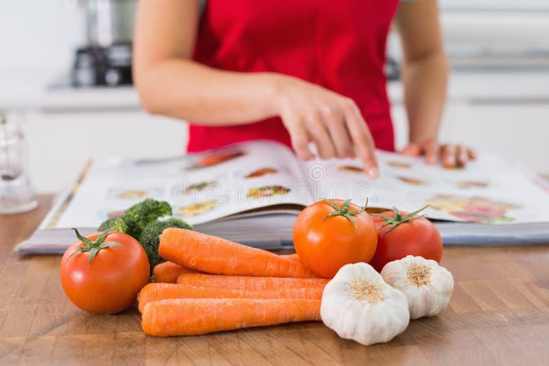 W połowie sekcja kobieta z przepisów warzywami w kuchni i książką obrazy stock