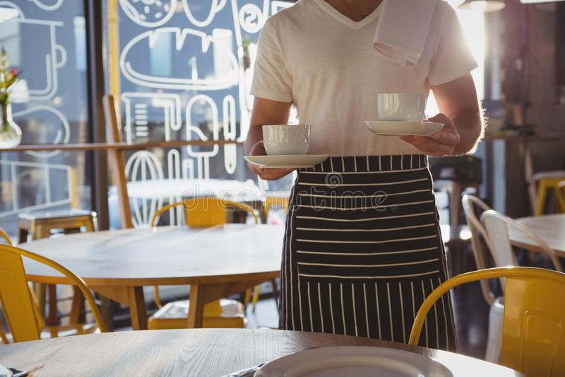 W połowie sekcja trzyma filiżanki kelner obraz royalty free