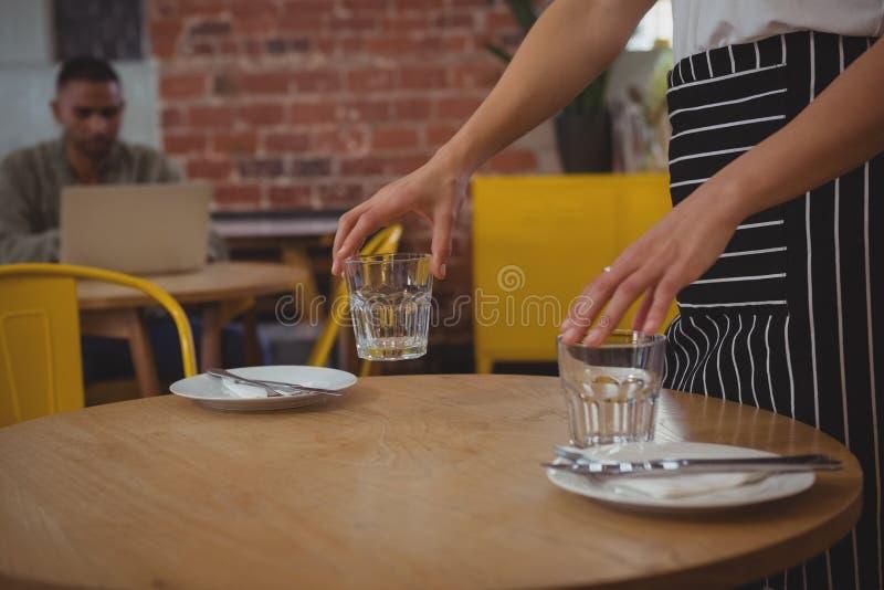 W połowie sekcja układa szkła na stole kelnerka obrazy royalty free