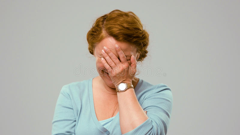 W połowie starzeć się aktorka seansu oferty emocje, zakrywa jej twarz z palmą zdjęcie stock