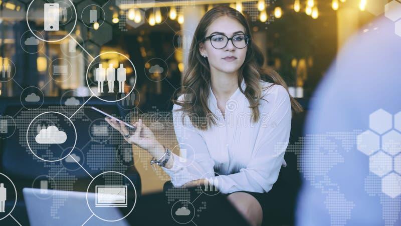 W przedpolu są wirtualne ikony z chmurami, ludzie, gadżety biznesowego biznesmena cmputer biurka laptopu spotkania ja target1953_ fotografia stock