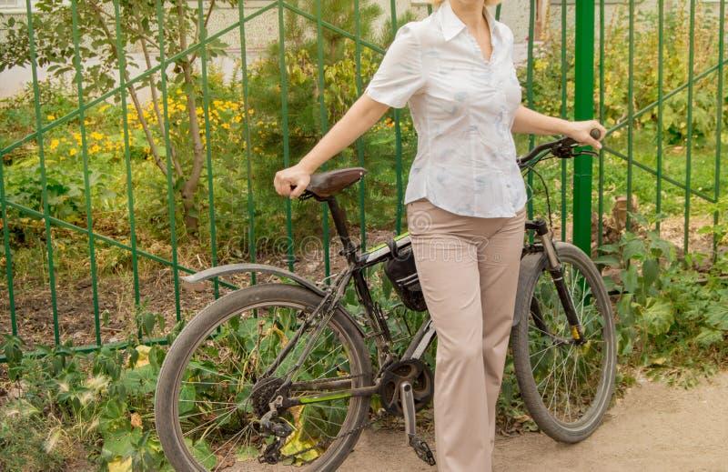 W ?rednim wieku atrakcyjna szczup?a kobieta w lekkich spodniach i koszula stojakach blisko roweru w parku na Pogodnym letnim dniu zdjęcia royalty free