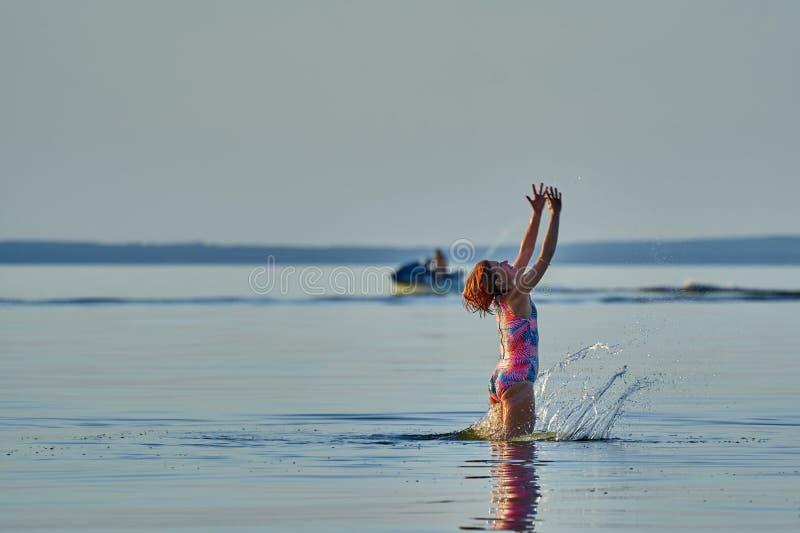 W ?rednim wieku kobieta z czerwonym w?osy i swimsuit odbija si? w wodzie wielki jezioro obraz royalty free