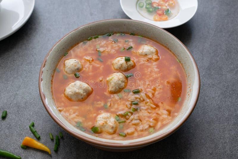 W?rzige Suppe des Reises mit H?hnerball und Paprikas in der grauen Sch?ssel auf Tabelle lizenzfreie stockbilder