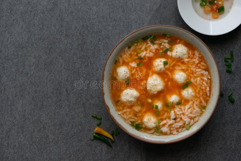 W?rzige Suppe des Reises mit H?hnerball und Paprikas in der grauen Sch?ssel auf Tabelle lizenzfreie stockfotos