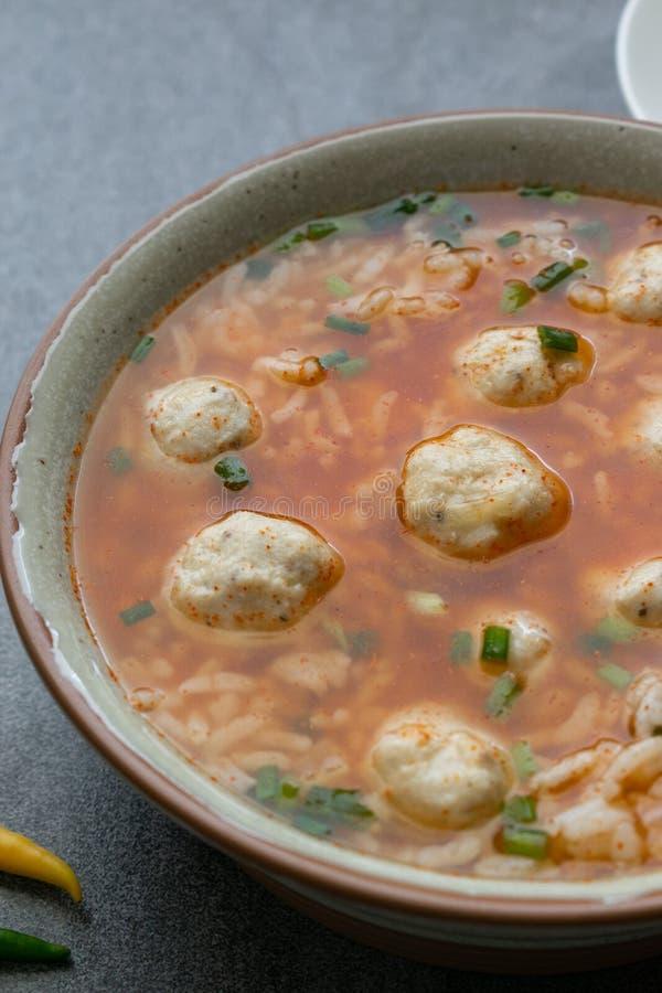 W?rzige Suppe des Reises mit H?hnerball und Paprikas in der grauen Sch?ssel auf Tabelle stockbilder