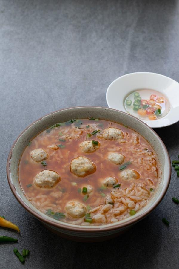 W?rzige Suppe des Reises mit H?hnerball und Paprikas in der grauen Sch?ssel auf Tabelle lizenzfreies stockbild