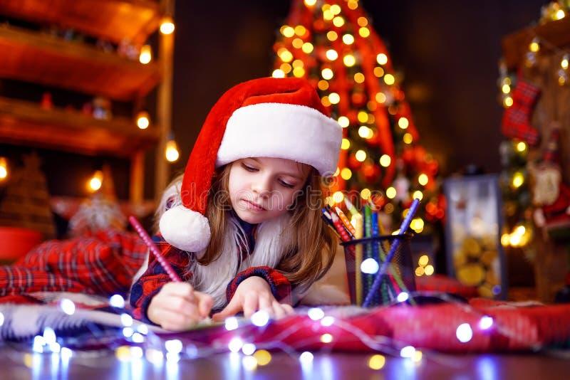 W Santa kapeluszu śmieszna dziewczyna pisze liście Santa obrazy royalty free