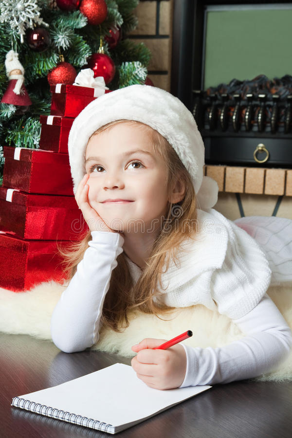 W Santa kapeluszu śmieszna dziewczyna pisze liście Santa zdjęcia stock