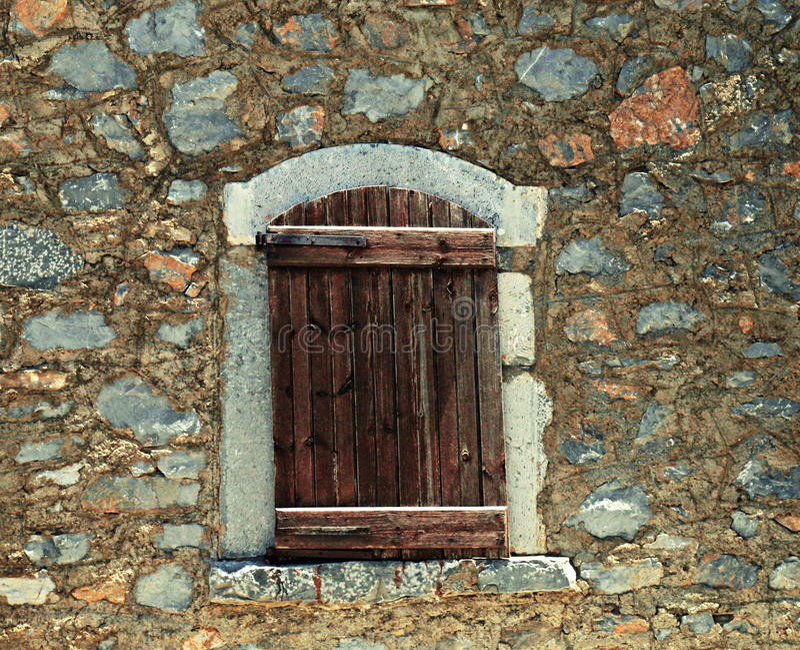W starej kamiennej ścianie szorstkie drewniane żaluzje zdjęcia royalty free
