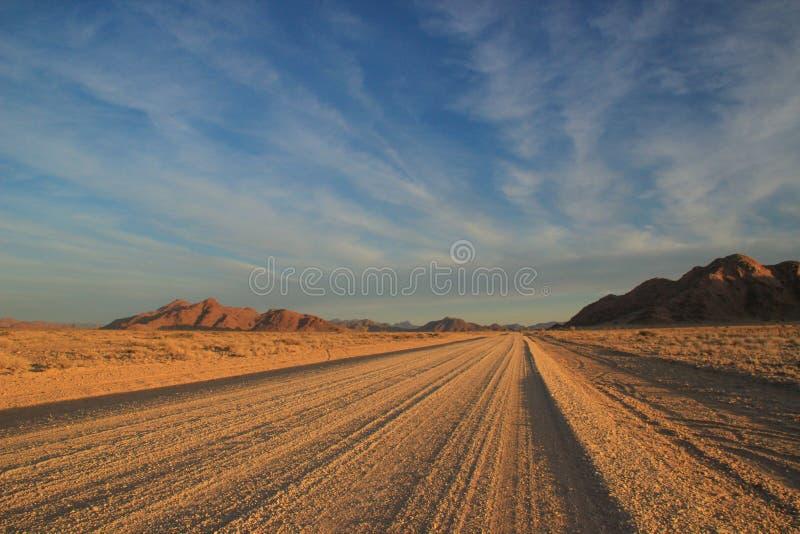 W?stenlandschaften mit Bergen und der Stra?e im S?den von Namibia stockbilder