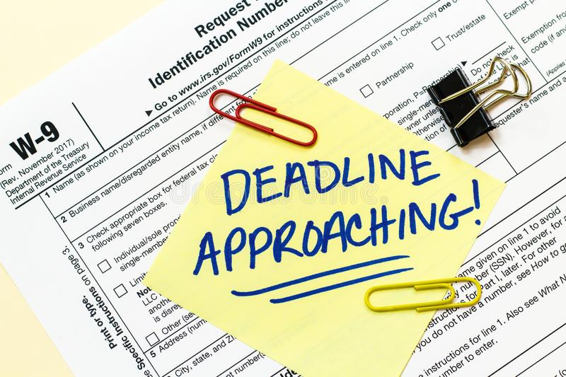 W9 Tax Form Deadline Approaching Concept. A W9 tax form with DEADLINE APPROACHING written on a yellow sticky note royalty free stock image