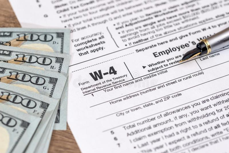 W4 tax form with money. And pen stock photo