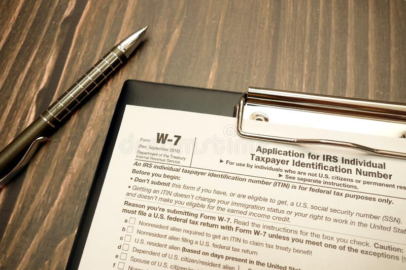 W-7 tax form with pen on wooden desk. Tax form W-7 for Non-US-citizens for avoid US withholding tax and pen on wooden desk stock images