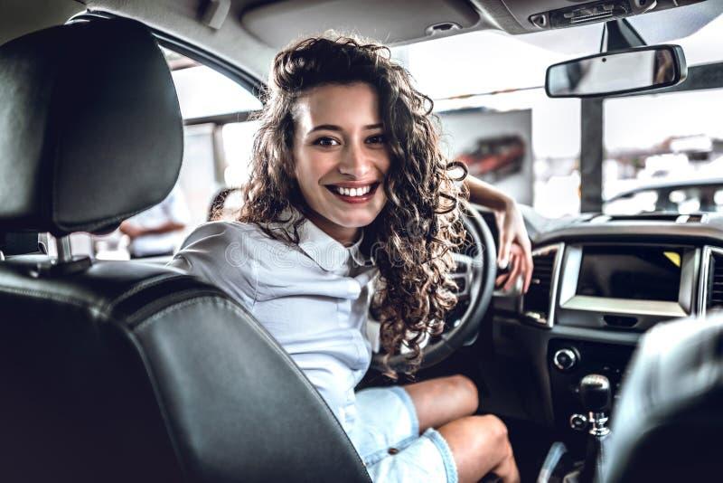 W ten sposób szczęśliwy! Piękna młoda szczęśliwa kobieta pozuje wśrodku nowego samochodu fotografia royalty free