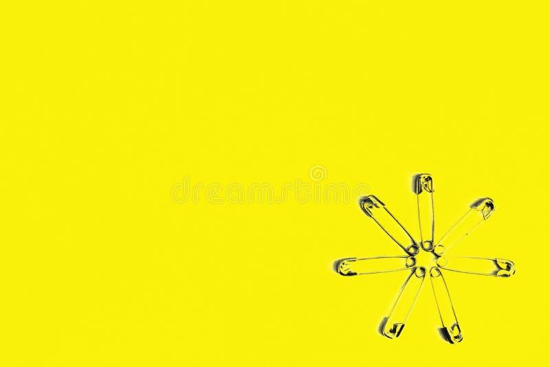 W tle dla teksta są wiele szpilki składać w formie kwiatu na żółtym tle ilustracji