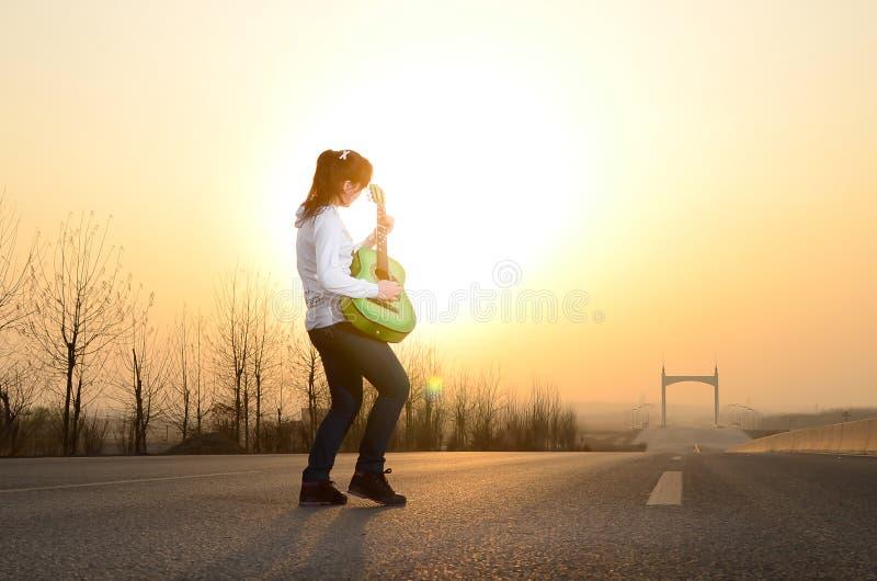W wieczór, dziewczyna bawić się gitarę na drodze fotografia royalty free