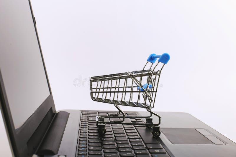 W?zek na zakupy jest na laptopie Online sprzeda?y poj?cie fotografia stock