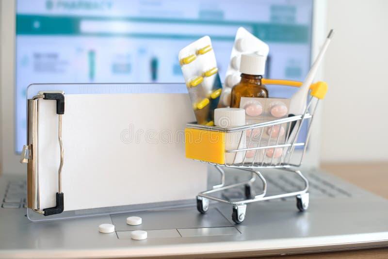 W?zek na zakupy zabawka z medicaments i papier notatka przed laptopu ekranem z apteki stron? internetow? na nim obrazy royalty free