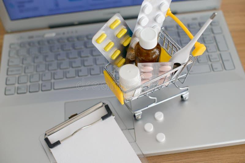 W?zek na zakupy zabawka z medicaments i papier notatka przed laptopu ekranem z apteki stron? internetow? na nim zdjęcia royalty free