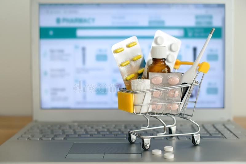 W?zek na zakupy zabawka z medicaments przed laptopu ekranem z apteki stron? internetow? na nim fotografia royalty free