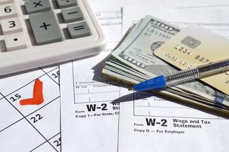 W-2 Zestawienie płac i podatków puste z kartą kredytową na banknoty, kalkulator i pióro na stronie kalendarza z zaznaczonym 15 kw obraz royalty free