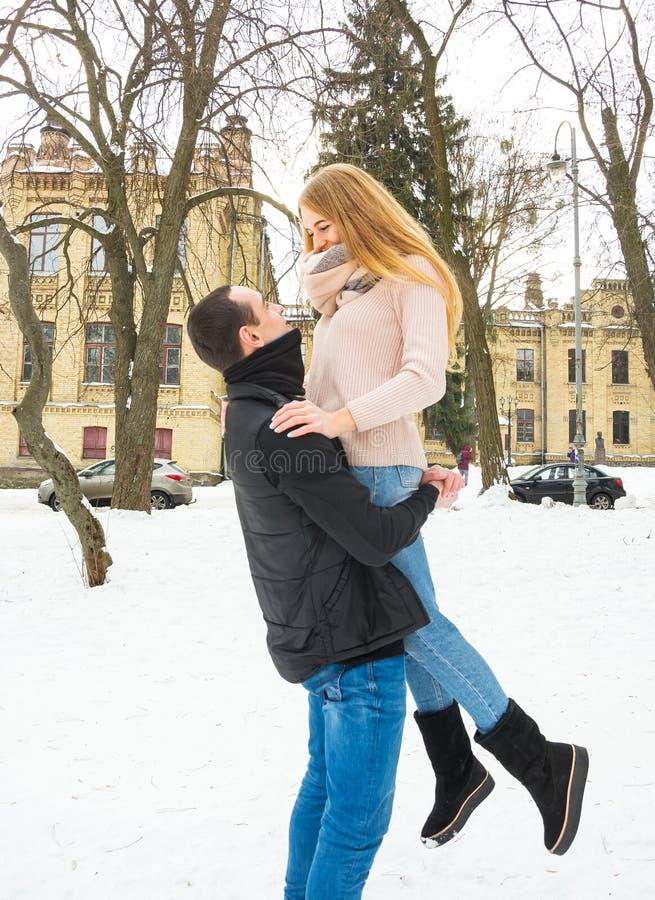 W zima kochająca para Facet podnosi dziewczyny w jego rękach na ulicie w zimie obraz royalty free