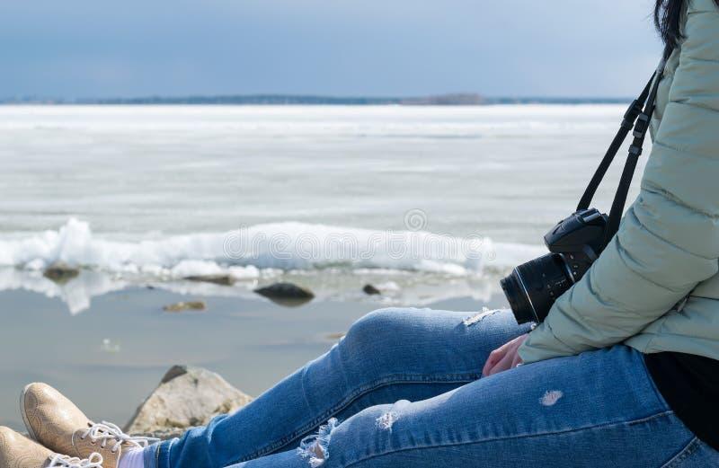 W zimie dziewczyna siedzi na wybrzeżu na tle lodowaty jezioro zdjęcia royalty free