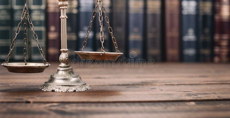 Waży sprawiedliwości i prawa książki na drewnianym tle fotografia stock