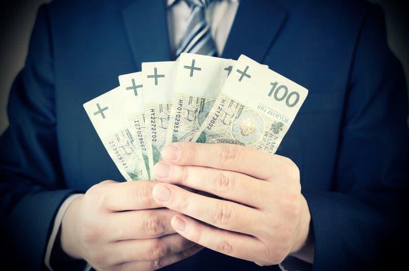 Waaier van Poolse bankbiljetten in zakenmanhand stock fotografie