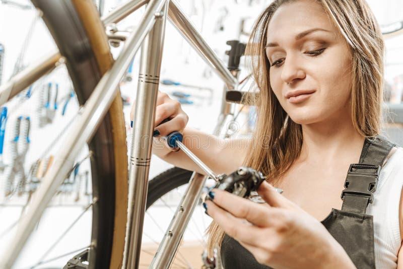 Waakzame prettige craftswoman herstellend het pedaal in de garage royalty-vrije stock afbeeldingen