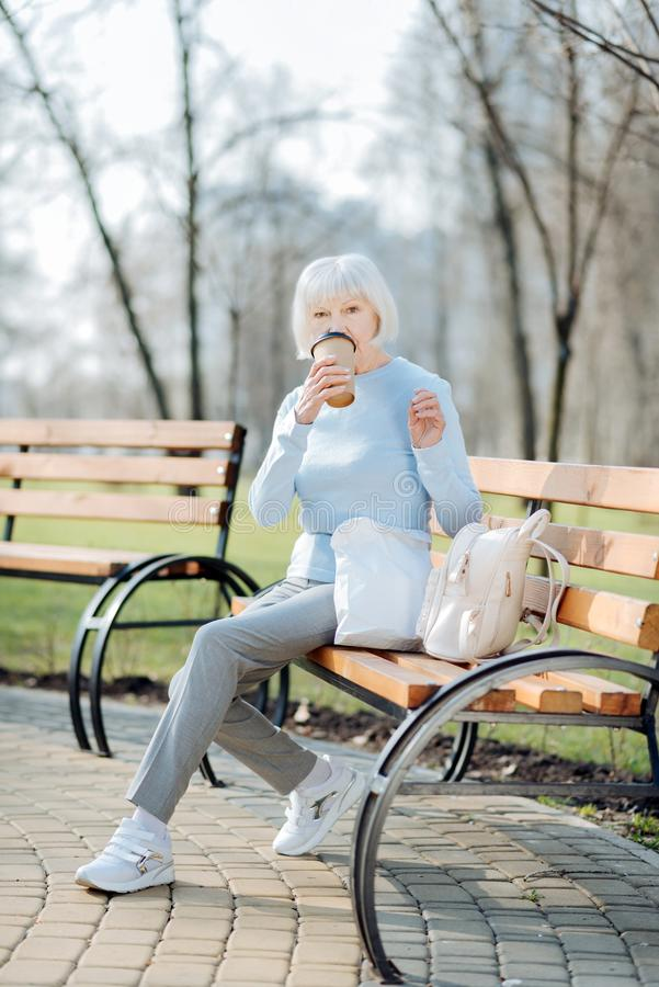 Waakzame vrouw het drinken koffie terwijl het zitten op de bank royalty-vrije stock afbeeldingen