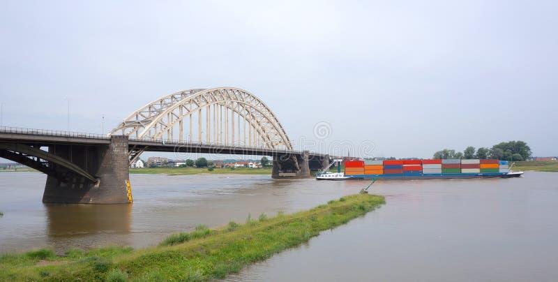 Waalbrug bridge, Nijmegen, the Netherlands. A container transport boat under Waalbrug bridge over the river Waal near Nijmegen, the Netherlands stock photography