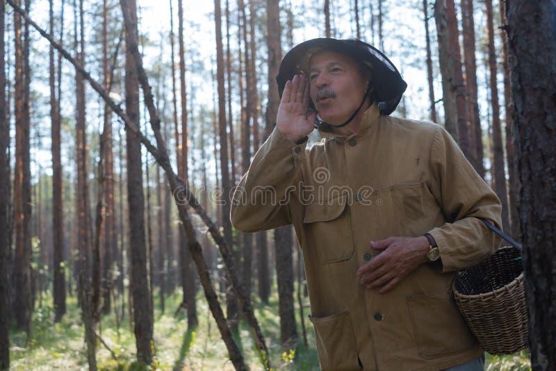 Waar u concept bent De rijpe Europese mens gekleed in oude kleren die mand houden wordt verloren in bos royalty-vrije stock afbeelding