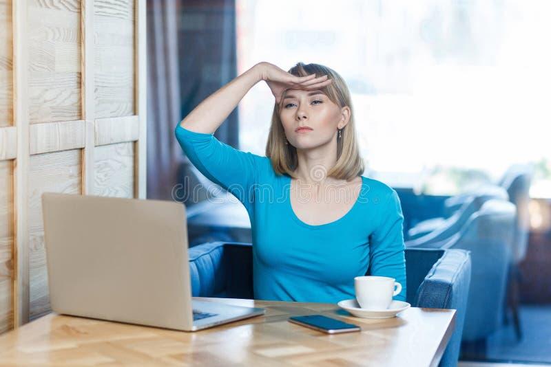 Waar u? Het portret van ernstige jonge onderneemster in blauwe t-shirt zit in koffie en houdt haar hand dichtbij voorhoofd stock fotografie