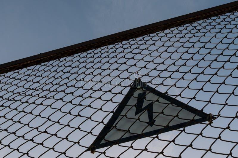 Waarschuwend driehoekig teken met bliksemsymbool op de omheining Levensgevaarlijk Geen ingang Hoogspanningsconcept Silhouet stock foto's