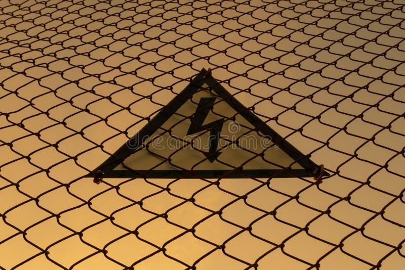 Waarschuwend driehoekig teken met bliksemsymbool op de omheining Levensgevaarlijk Geen ingang Hoogspanningsconcept Zonsondergang royalty-vrije stock foto's